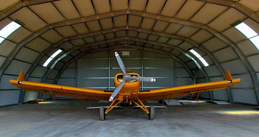 Orange Light aircraft parked inside a semicircle steel frame dry and easy to access building.